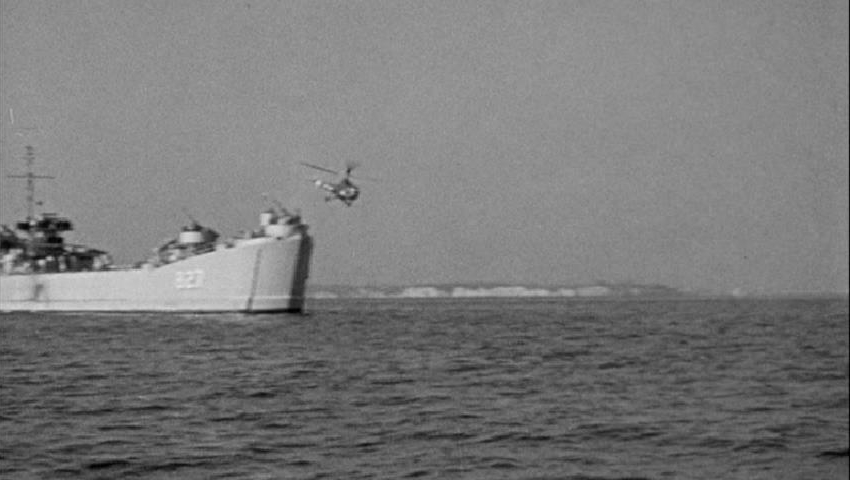 Helicopter lifts off from ship at sea.